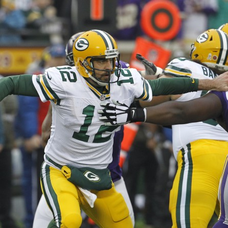 Green Bay Packers quarterback Aaron Rodgers, left, breaks a tackle by Minnesota Vikings defensive tackle Shamar Stephen (93) during the first half of an NFL football game, Sunday, Nov. 23, 2014, in Minneapolis. (AP Photo/Ann Heisenfelt) ORG XMIT: MNCN102